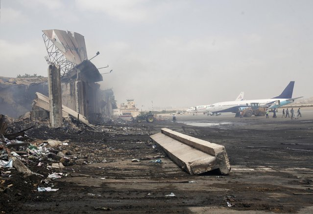 Planes are seen near a section of a damaged building at Jinnah International Airport, after Sunday's attack by Taliban militants, in Karachi June 10, 2014. REUTERS/Athar Hussain