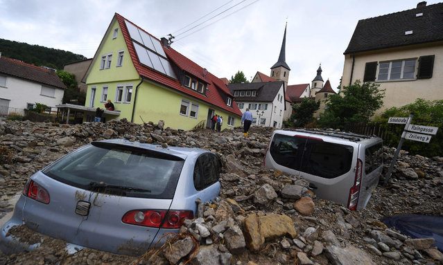 Cars are buried under debris in Braunsbach, Germany, 30 May 2016. Torrential rainfalls caused two smalll brooks to burst their banks with the resulting flooding of the streets causing severe damage to cars and houses in the southern German village. (Photo by Marijan Murat/EPA)