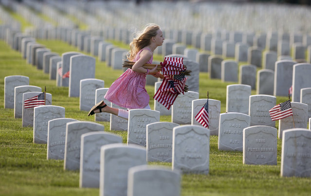 Boston Downs, 9, of Hampton, Va. runs along a row of graves at Hampton National Cemetery carrying a bundle of flags to her mom, Stephanie and brother Sullivan, 6, Friday, May 26, 2017 in Hampton, Va.. They came to the cemetery Friday morning with other volunteers to place a flag at each of the veteran's graves. Boston's dad is Navy Lt. Chad Downs who serves aboard the aircraft carrier Eisenhower. (Photo by Bill Tiernan/The Virginian-Pilot via AP Photo)