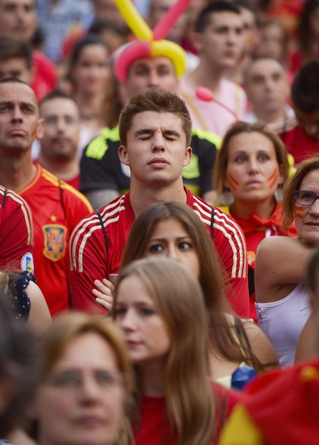 A Spain fan reacts as she watches the FIFA World Cup 2014 football match between Spain and Chilli in Brazil, on a large screen in Madrid on June 18, 2014. (Photo by Dani Pozo/AFP Photo)
