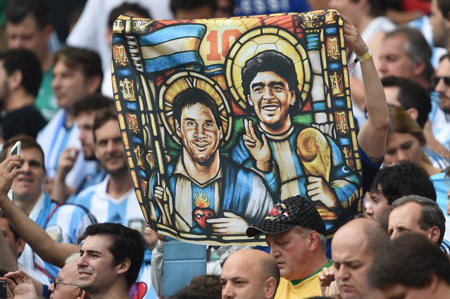 An Argentina's fan holds an image of Argentina's forward Lionel Messi and former footballer Diego Maradona as saints, before for the Group F football match between Nigeria and Argentina at the Beira-Rio Stadium in Porto Alegre during the 2014 FIFA World Cup on June 25, 2014. (Photo by Pedro Ugarte/AFP Photo)