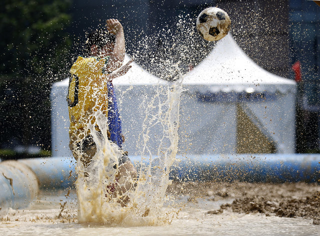 A player kicks a ball during a match at the swamp soccer China tournament in Beijing, June 26, 2014. The 32 teams from across the country participated in the soccer event to celebrate the 2014 World Cup in Brazil. (Photo by Kim Kyung-Hoon/Reuters)
