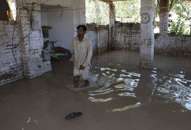 A man retrieves an item from his home after heavy rainfall caused flooding in Peshawar, Pakistan, July 27, 2015. (Photo by Khuram Parvez/Reuters)