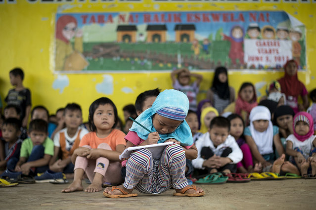 """Johainah Nasrodeng, 5, writes in her notebook at a makeshift classroom for student evacuees at the Pantar Central Elementary School in Pantar, Lanao del Norte on the southern island of Mindanao on June 6, 2017. The schoolchildren, some 238 of them with their parents fled by foot for eight hours from Marawi City to Pantar municipality in a bid to escape heavy fighting. With bomb-proof tunnels, anti-tank weapons hidden in mosques, human shields and a """"mastery"""" of the terrain, Islamist militants holed up in a southern Philippine city are proving a far tougher opponent than military chiefs expected. (Photo by Noel Celis/AFP Photo)"""