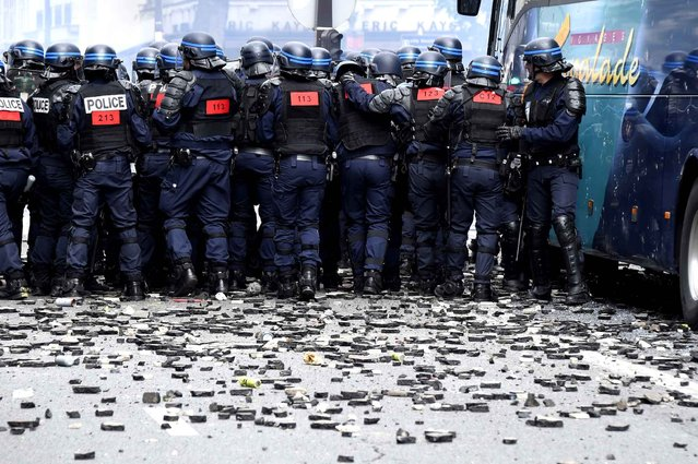 French anti-riot police officers stand as stones and rubbish lie on the pavement during a demonstration against proposed labour reforms near the Hopital Necker in Paris on June 14, 2016. Several hundred masked protesters hurled objects at police on June 14 during a demonstration in Paris against a contested reform of French labour laws, authorities said. (Photo by Dominique Faget/AFP Photo)