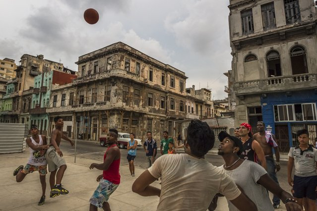 Young men play basketball on an improvised court wedged between a construction site and the shells of once grand colonial homes in Havana, July 20, 2015. As much as the young in Cuba welcome political opening and economic reform, such changes are unlikely to filter down to their lives anytime soon. (Photo by Meridith Kohut/The New York Times)