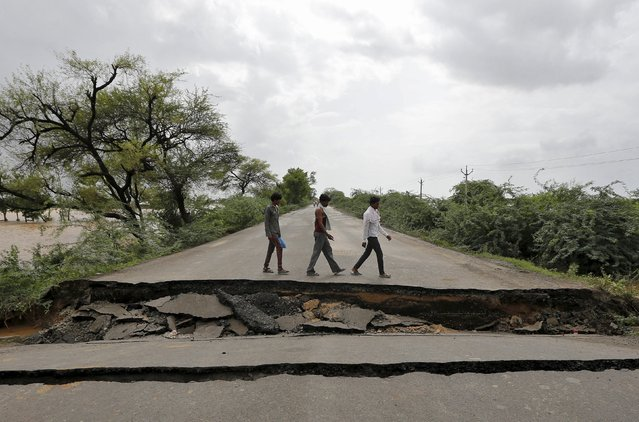 People prepare to cross the damaged national highway after heavy rains on the outskirts of Ahmedabad, India, July 31, 2015. At least 26 people have been killed in the flood-like situation caused by torrential monsoon rains in some parts of the western Indian state of Gujarat, local media reported on Thursday. (Photo by Amit Dave/Reuters)