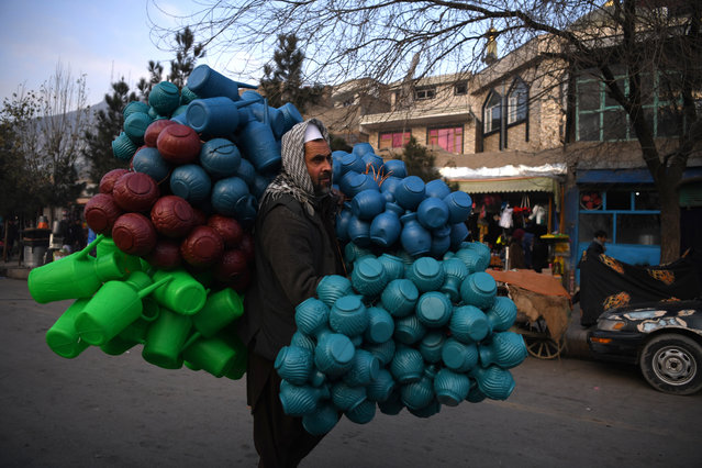 A man carries plastic pitchers on a street in Kabul on December 19, 2019. (Photo by Farshad Usyan/AFP Photo)