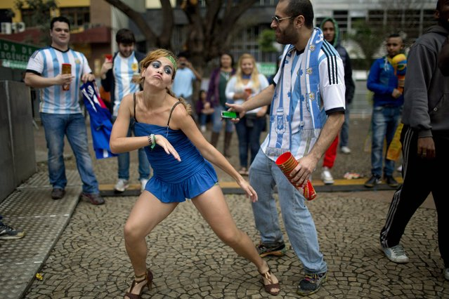 A Brazilian national soccer fan, left center, dances with an Argentine fan as they wait for start of the live telecast of the World Cup semifinal match between Argentina and the Netherlands, at FIFA Fan Fest in Sao Paulo, Brazil, Wednesday, July 9, 2014. (Photo by Rodrigo Abd/AP Photo)