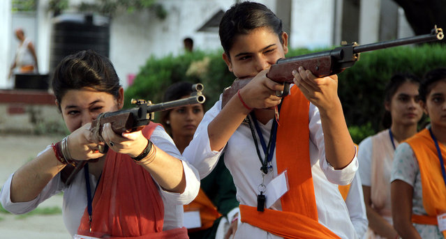 Indian girls of Durga Vahini, a Hindu hardliner women's organization take part in week-long self defense training camp in Jammu, the winter capital of Kashmir, India, July 7, 2014. In the wake of the increase in crime against women in the country these young girls are being given training to operate sticks and guns and to develop the skills of self defense. (Photo by Jaipal Singh/EPA)