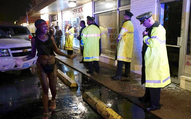 A woman taunts police standing outside the looted Bowen Beauty Supply at the site of last year's riots on the one year anniversary of the killing of Michael Brown in Ferguson, Missouri August 9, 2015. (Photo by Rick Wilking/Reuters)