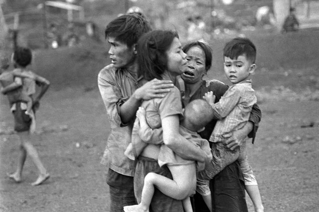 In this June 1965 photo, South Vietnamese civilians, among the few survivors of two days of heavy fighting, huddle together in the aftermath of an attack by government troops to retake the post at Dong Xoai, Vietnam