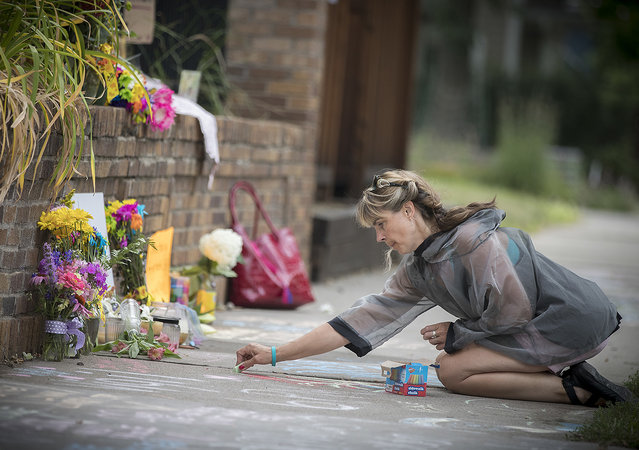 Megan O'Leary, of St. Paul, leaves a message on the sidewalk near the scene where a Minneapolis police officer shot and killed Justine Damond, of Australia, Monday, July 17, 2017, in Minneapolis. Relatives and neighbors of the Australian woman fatally shot by Minneapolis police over the weekend demanded answers Monday about the mysterious shooting in which the meditation teacher was reportedly killed by an officer who fired from the passenger seat of a squad car as the woman stood outside the driver's door. (Photo by Elizabeth Flores/Star Tribune via AP Photo)