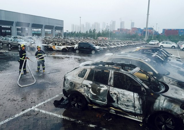 Firefighters work at a parking lot at the site of explosions at the Binhai new district in Tianjin August 13, 2015. Two massive explosions caused by flammable goods ripped through an industrial area in the northeast Chinese port city of Tianjin late on Wednesday, killing 17 people and injuring around 400, official Chinese media reported. (Photo by Reuters/Stringer)
