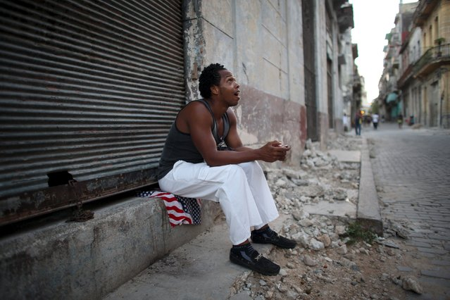 Dancing teacher Yeni Acosta, 19, sits on the sidewalk as he chats on his mobile phone in downtown Havana, August 6, 2015. (Photo by Alexandre Meneghini/Reuters)