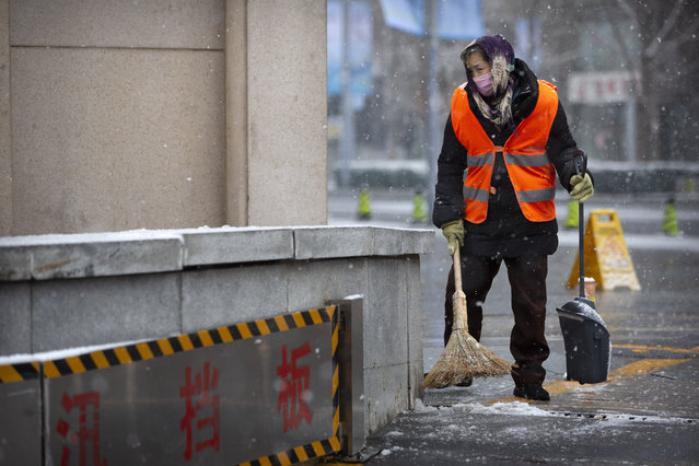 A maintenance worker wears a face mask as she sweeps snow during a snowfall in Beijing, Sunday, February 2, 2020. China's death toll from a new virus increased to 304 on Sunday amid warnings from the World Health Organization that other countries need to prepare in the event the disease spreads among their populations as more nations report local infections. (Photo by Mark Schiefelbein/AP Photo)