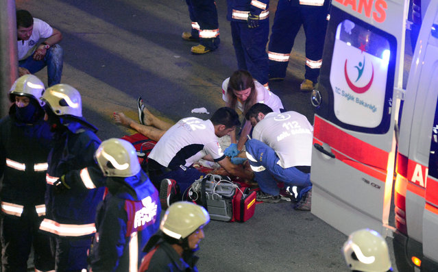 Turkish rescue services members help a wounded person outside Istanbul's Ataturk airport, Tuesday, June 28, 2016. (Photo by Ismail Coskun/IHA via AP Photo)