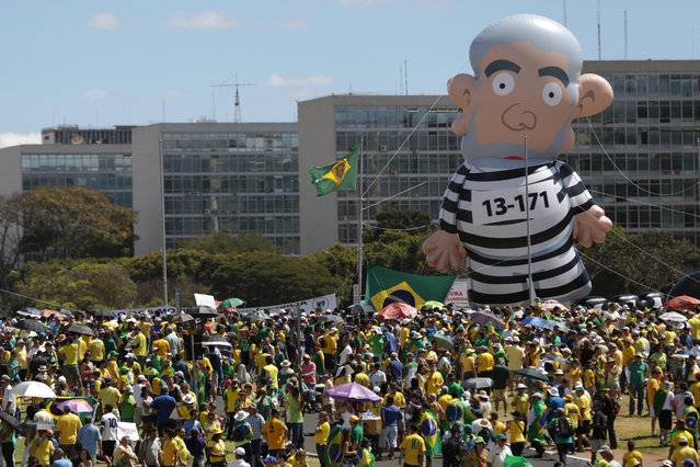 A large inflatable doll dressed in prison garb and in the image of the Brazil's Former President Luiz Inacio Lula da Silva, is seen during a protest against the government of Brazil's President Dilma Rousseff, in front of the Brazilian National Congress, in Brasilia, Brazil, Sunday, August 16, 2015. (Photo by Eraldo Peres/AP Photo)