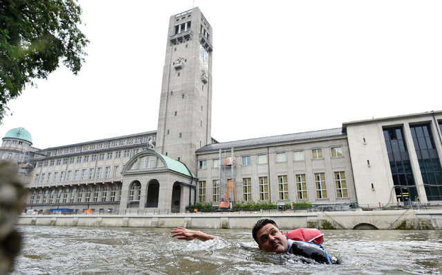 Benjamin David passes the Deutsches Museum as he swims from his home to his workplace along the Isar River in Munich, Germany, August 10, 2017. (Photo by Andreas Gebert/Reuters)