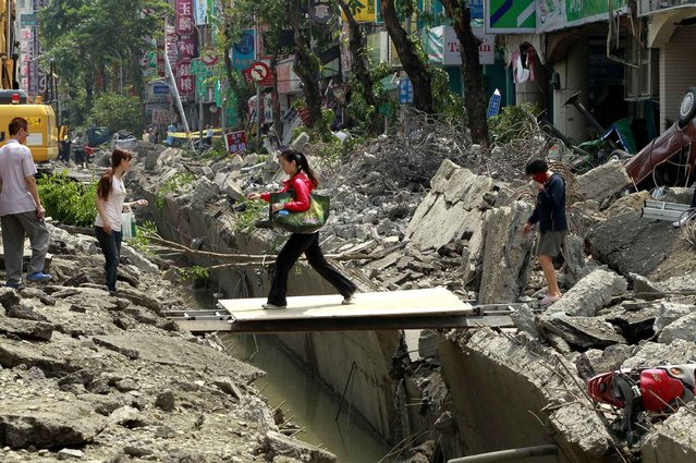 A woman crosses over a trench made from a massive gas explosion in Kaohsiung, Taiwan, Friday, August 1, 2014. Scores of people were killed and more than 200 others injured when several underground gas explosions ripped through Taiwan's second-largest city overnight, hurling concrete through the air and blasting long trenches in the streets, authorities said Friday. (Photo by Wally Santana/AP Photo)