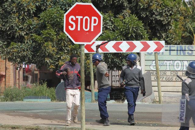 Armed Zimbabwean police beat an alleged rioter in Harare, Monday, July, 4, 2016. (Photo by Tsvangirayi Mukwazhi/AP Photo)