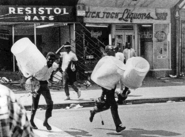 In this August 13, 1965 file photo, men carry items from a looted store during the rioting that enveloped the Watts district of Los Angeles. It began with a routine traffic stop 50 years ago this month, blossomed into a protest with the help of a rumor and escalated into the deadliest and most destructive riot Los Angeles had seen. The Watts riot broke out Aug. 11, 1965 and raged for most of a week. When the smoke cleared, 34 people were dead, more than a 1,000 were injured and some 600 buildings were damaged. (Photo by AP Photo)
