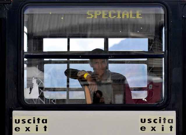 A migrant looks out from a bus window following their arrival onboard the Italian Coast Guard vessel Diciotti in the Sicilian harbour of Palermo, Italy, August 20, 2015. (Photo by Guglielmo Mangiapane/Reuters)