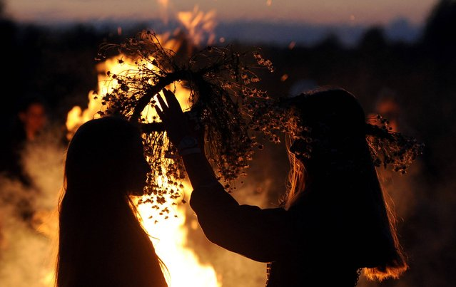 Two girls put traditional wreaths near a bonfire as they take part in the Ivan Kupala Night celebration, a traditional Slavic holiday, outside the small town of Turov, some 270 km south of Minsk, on July 6, 2016. People celebrate Kupala Night with bonfires that last throughout the night with some leaping over the flames as it is believed that the act of jumping over the bonfire cleanses people of illness and bad luck. (Photo by Sergei Gapon/AFP Photo)