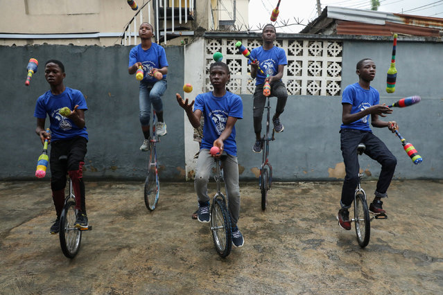 Members of the GKB academy, a unicycle club, juggle while balancing on their unicycles during a training session in Lagos, Nigeria on October 11, 2019. (Photo by Temilade Adelaja/Reuters)