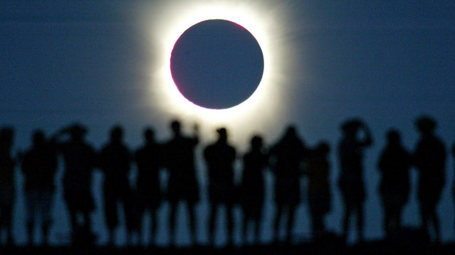 Tourists watch the sun being blocked by the moon during a solar eclipse in the Australian outback town of Lyndhurst, located around 700 kilometres (437 miles) north of Adelaide December 4, 2002. (Photo by David Gray/Reuters)