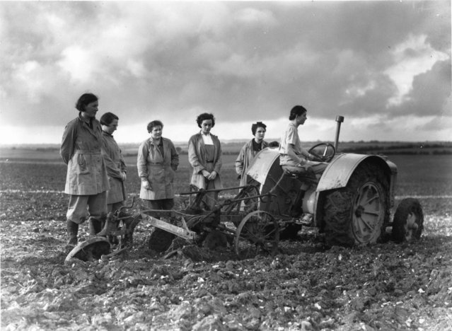 A few months after the start of world war II members of the Women's Land Army stand round their tractor plough observing a minute's silence in honour of Armistice Day for the 1st world war! 11th November 1939.  (Photo by Fox Photos)