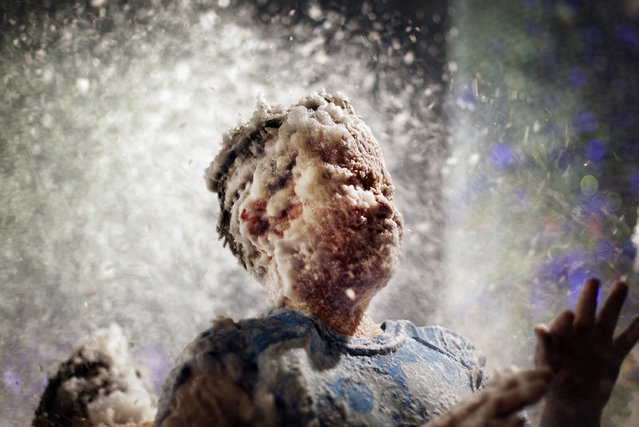 Children's faces are covered with foam used to simulate snow at a shopping mall on Tuesday, December 14, 2010 in Singapore where malls are taking advantage of the festive season to draw in customers through visual merchandising, advertising and year end sales. (Photo by Wong Maye-E/AP Photo)
