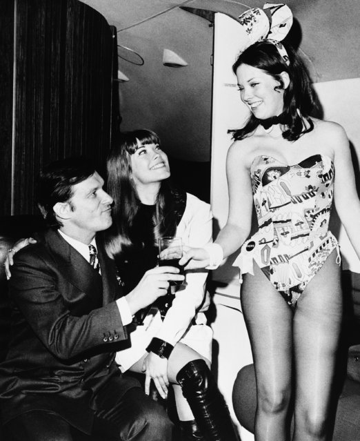 Hugh Hefner, left, and girlfriend Barbi Benton, center, are served by N.Y. Playboy Club Bunny Cheri upon arrival at La Guardia aboard the Big Bunny, Heffners personal 5? million dollar DC-9 jet, March 1970, New York. Hefner is in New York for two days of business conferences and personal appearances in connection with his far-flung Playboy Empire. (Photo by AP Photo)