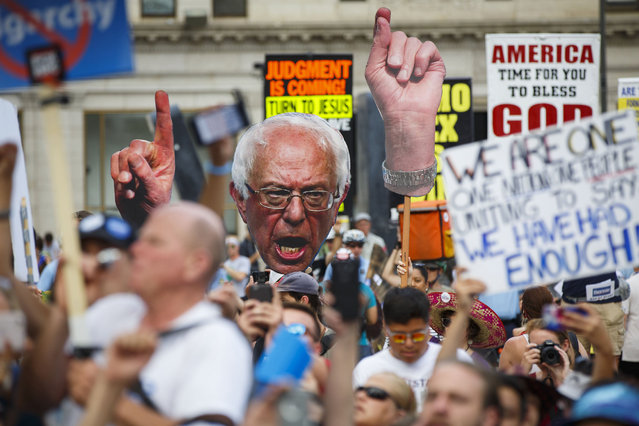 "Supporters of former Democratic presidential candidate Bernie Sanders hold up posters at a ""Black Men For Bernie"" rally to gain support for third party candidates and protest the DNC during the 2016 Democratic National Convention on July 27, 2016 in Philadelphia, Pennsylvania. (Photo by Patrick T. Fallon/AFP Photo)"