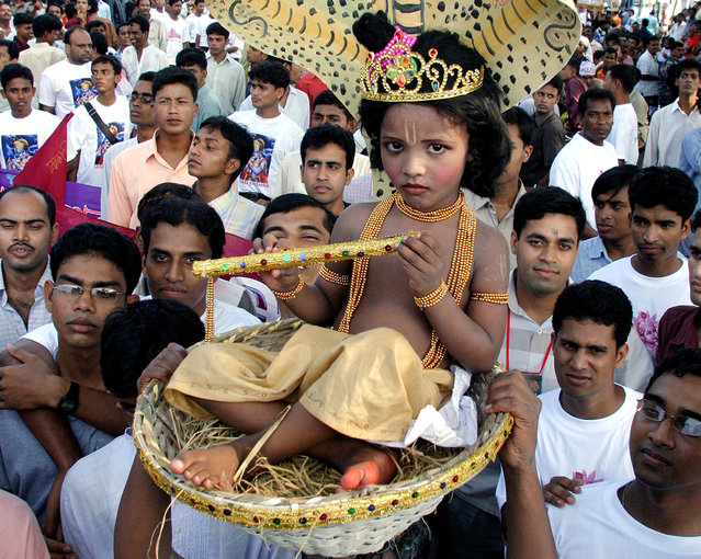Bangladeshi members of Hindu community carry boy dressed as Krishna during celebrations of birthday of Lord krishna in Dhaka on August 26, 2005. (Photo by Rafiqur Rahman/Reuters)