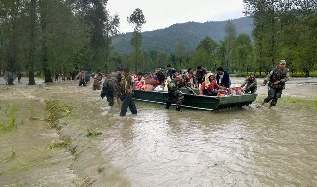 Indian army soldiers evacuate flood-affected people in Jammu, India, Saturday, September 6, 2014. Heavy monsoon rains have caused flash floods and landslides that left more than 100 people dead in the disputed Himalayan region of Kashmir and in eastern Pakistan, officials said Friday. (Photo by AP Photo/Press Trust of India)