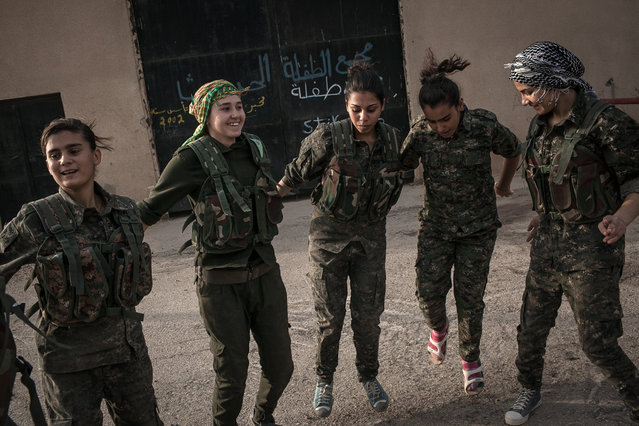 Young YPJ recruits take a break by dancing and singing traditional YPJ songs at dawn, near Derek City, Syria.  The YPJ schedule is demanding and requires discipline - new soldiers in training get about 6 hours of sleep a night and wake up at 4 AM; their day consists of a full schedule of drills and classroom lessons. Before joining the YPJ many of the girls had never participated in physical activity or sports before. (Photo by Erin Trieb/NBC News)