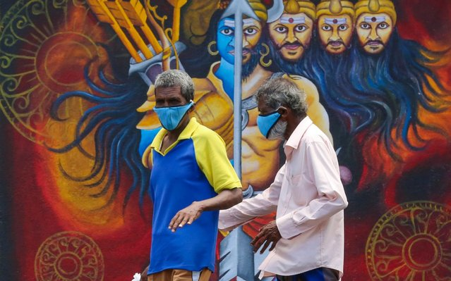 Two daily-wage workers wear protective face masks as they walk in front of a mural during an island-wide curfew, in Colombo, Sri Lanka, 14 April 2020. The Sri Lankan government has implemented an island-wide curfew until further notice in order to slow down the spread of the SARS-CoV-2 coronavirus that causes the COVID-19 disease. (Photo by Chamila Karunarathne/EPA/EFE/Rex Features/Shutterstock)