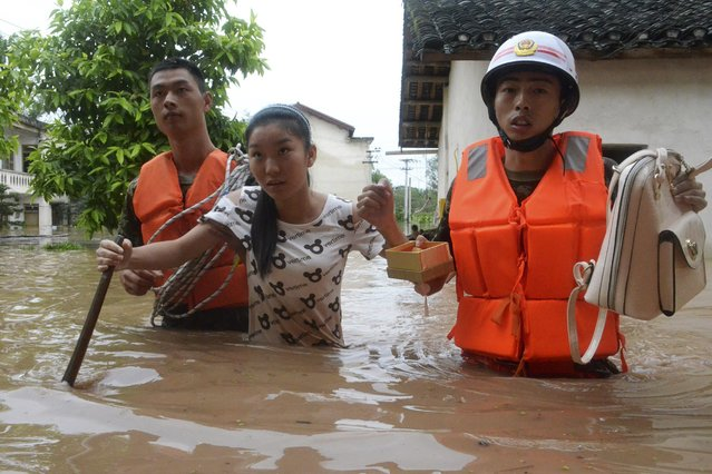 Rescuers help a woman get to dry area as they walk among floodwater after heavy rainfall hit Chongqing municipality, September 13, 2014. At least 10 people died after severe downpours battered southwest China's Sichuan Province and Chongqing Municipality, Xinhua News Agency reported. (Photo by Reuters/Stringer)