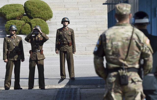 North Korean soldiers, left, look at the South side while U.S. Defense Secretary Jim Mattis and South Korean Defense Minister Song Young-moo visit the truce village of Panmunjom in the Demilitarized Zone (DMZ) on the border between North and South Korea Friday, October 27, 2017. (Photo by Jung Yeon-je/Pool Photo via AP Photo)