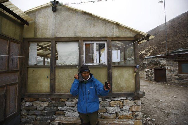 Trekking guide Birbal Thapa Magar makes an emergency phone call to check on his clients' health, in Pheriche, approximately 4,300 meters above sea level, in Solukhumbu District May 3, 2014. (Photo by Navesh Chitrakar/Reuters)