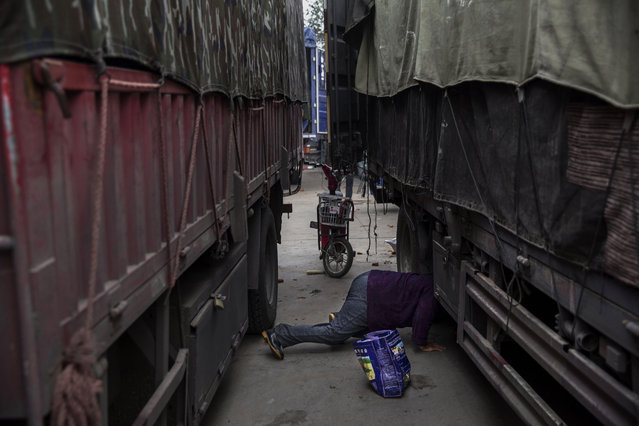 A poor elderly Chinese woman searches for vegetables that have fallen off a truck at a local market on September 26, 2014 in Beijing, China. (Photo by Kevin Frayer/Getty Images)