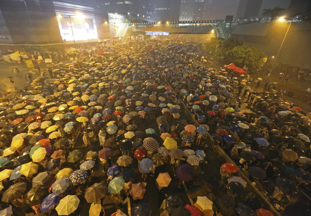 Pro-democracy protesters hold umbrellas under heavy rain in a main street near the government headquarters in Hong Kong late Tuesday, September 30, 2014. The protesters demanded that Hong Kong's top leader meet with them on Tuesday and threatened wider actions if he did not, after he said China would not budge in its decision to limit voting reforms in the Asian financial hub. (Photo by AP Photo)