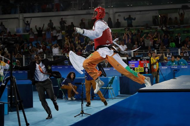 Cheick Sallah Junior Cisse of Ivory Coast jumps off the mat after defeating Lutalo Muhammad of Great Britain in the final seconds of the men's 80 kg taekwondo gold medal contest, August 20, 2016. (Photo by Gregory Bull/AP Photo)