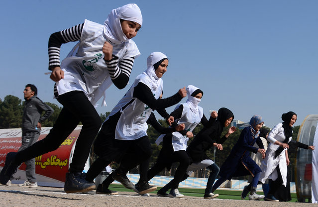 Afghan schoolgirls take part in a running race held for a peace initiative in Herat Province on November 11, 2016. (Photo by Aref Karimi/AFP Photo)