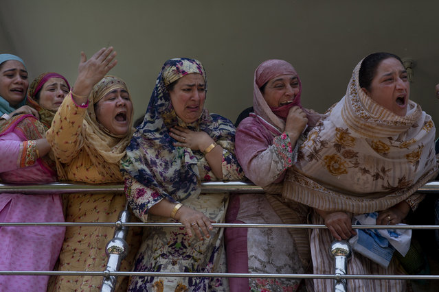 Relatives of Kashmiri civilian Bashir Ahmed Khan grieve as they watch his funeral on the outskirts of Srinagar, Indian controlled Kashmir, Wednesday, July 1, 2020. Suspected rebels attacked paramilitary soldiers in the Indian portion of Kashmir, killing Khan and a paramilitary soldier, according to government sources. The family refutes the claim. (Photo by Dar Yasin/AP Photo)
