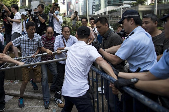 Anti-Occupy Central protesters (L) try to remove barricades set up as road blocks by pro-democracy protesters in the Central financial district in Hong Kong October 13, 2014. (Photo by Tyrone Siu/Reuters)
