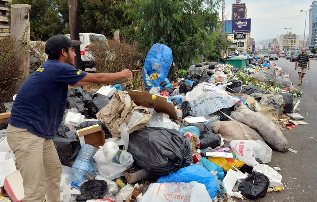 A man throws a bin bag onto a pile of garbage on a street in Jdeideh area, north east Beirut, Lebanon, 28 August 2016. The Christian Phalange Party (Kataeb) is refusing to dump waste in Burj Hammoud landfill and the garbage started to re-accumulate in eastern Beirut. Supporters of the Kataeb party set up the tent on 19 August at the entrance of the Burj Hammoud landfill site to prevent the government's plan to dump waste along the Metn coast. (Photo by Wael Hamzeh/EPA)
