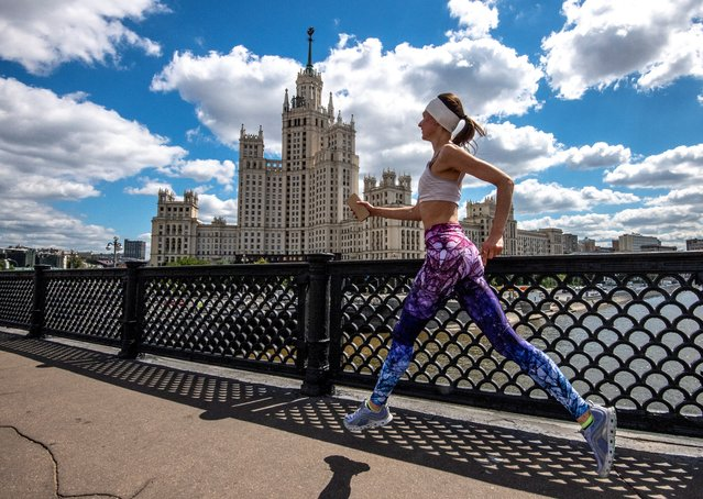 A woman runs along a bridge in front of a Stalin-era skyscraper in central Moscow on June 29, 2020. (Photo by Yuri Kadobnov/AFP Photo)
