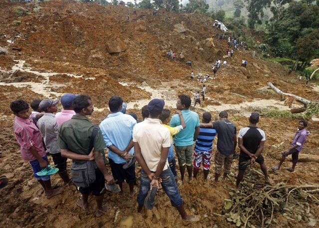 A group of men stand above the site of a landslide at the Koslanda tea plantation near Haldummulla October 30, 2014. (Photo by Dinuka Liyanawatte/Reuters)